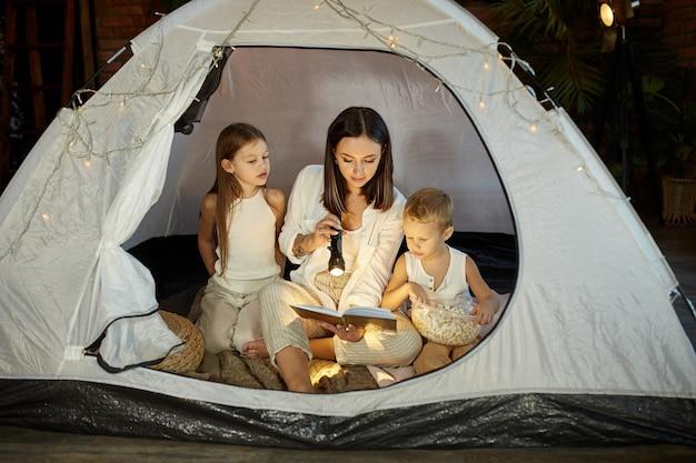 A mãe lê um livro de contos de fadas para crianças enquanto está sentada na barraca à noite