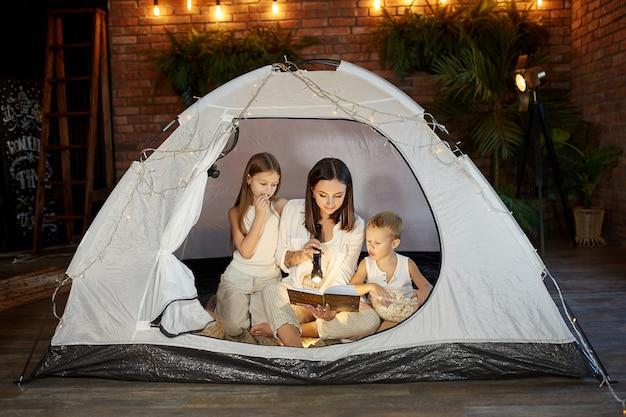 A mãe lê um livro de contos de fadas para os filhos enquanto está sentada em uma barraca à noite. mãe, filho e filha lendo um livro com uma lanterna nas mãos
