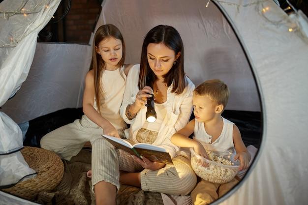 A mãe lê um livro de contos de fadas para os filhos enquanto está sentada em uma barraca à noite