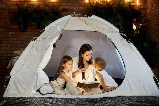 A mãe lê uma história para as crianças antes de dormir, sentada em uma barraca em casa. mãe, filho e filha se abraçam e leem um livro com uma lanterna nas mãos
