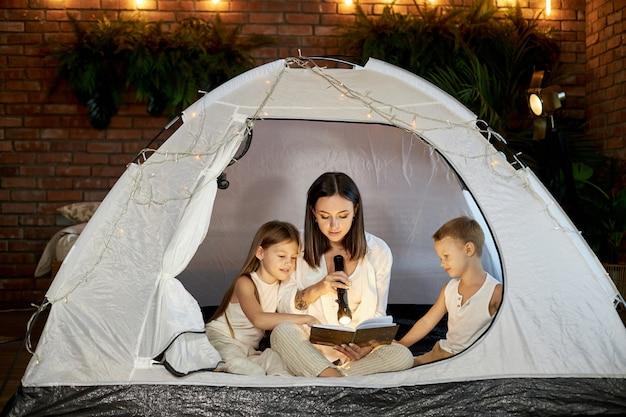 A mãe lê uma história para as crianças antes de dormir, sentada em uma barraca em casa