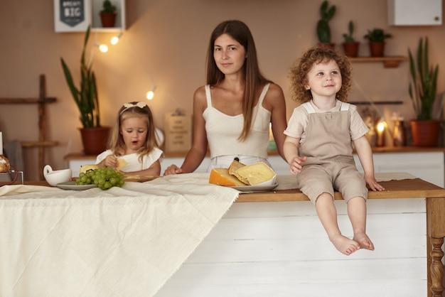 A mãe na cozinha prepara um café da manhã saudável para os filhos.