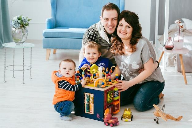A mãe, o pai e os filhos brincam com brinquedos