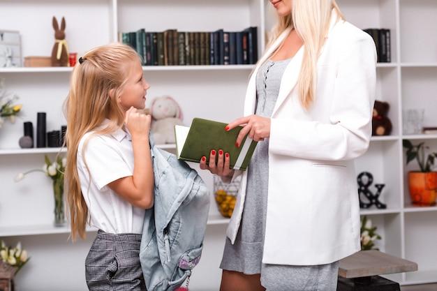 A mãe olha para o caderno de exercícios da criança e o coloca na pasta