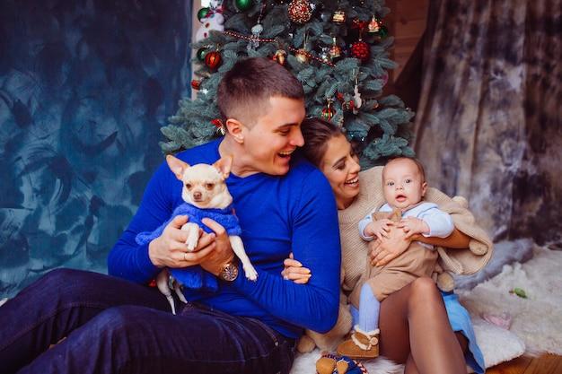A mãe, pai, cachorro e bebê sentados perto da árvore de natal