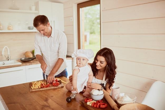 A mãe, pai e filho sentado na cozinha