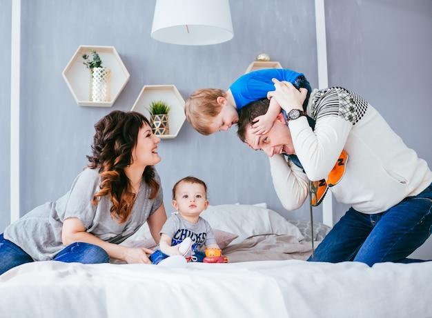 A mãe, pai e filhos sentados na cama