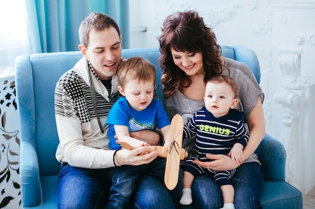 A mãe, pai e filhos sentados no sofá