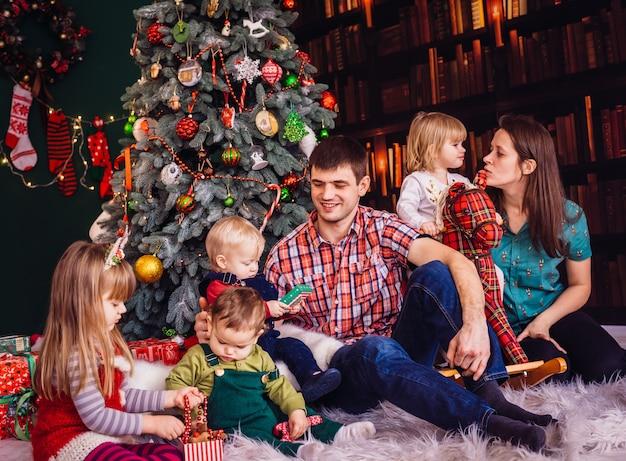 A mãe, pai e filhos sentados perto da árvore de natal