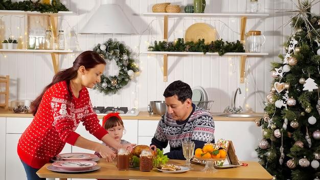 A mãe põe a mesa e o pai com a filha espera o jantar