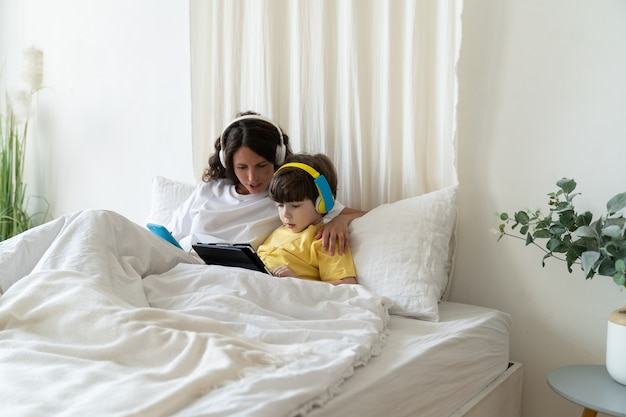 A mãe prefere educação em casa para criança pré-escolar deitada com a criança na cama, assista a vídeos educacionais e cursos de e-learning enquanto espera por uma ligação de negócios no celular de um parceiro ou cliente