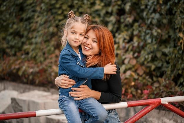 A mãe ruiva elegante e a filha dela estão falando calorosamente. criança feliz e a mãe dela na rua. mãe solteira de sucesso com a filha para passear. relacionamento familiar caloroso