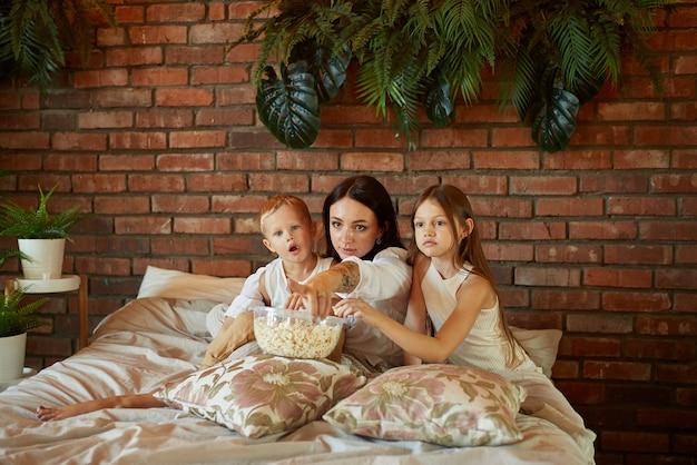 A mãe se senta na cama com seu filho e filha e assiste a um filme. mulher, menino e menina comem pipoca enquanto assistem filme no quarto