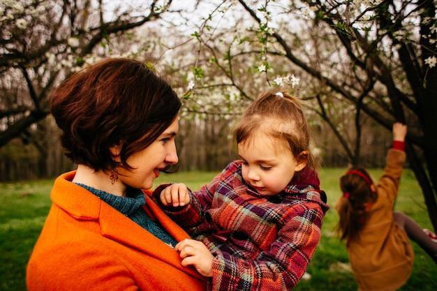A mãe segura as mãos da filha no parque