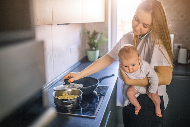A mãe segura o bebê nos braços. e cozinheiros na cozinha. mamãe fala ao telefone e está muito ocupada. conceito de multifuncionalidade.