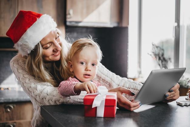A mãe senta-se com o filho pequeno na cozinha e faz compras online na loja online