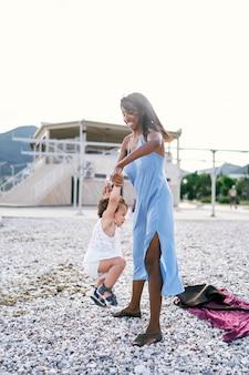 A mãe sorridente balança a menina pelos braços