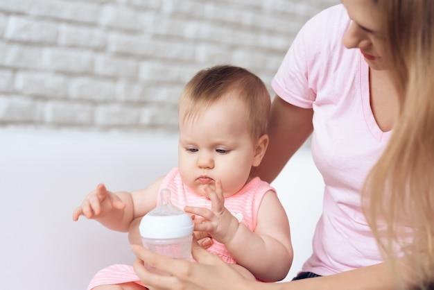 A mãe tenta alimentar em casa a garrafa de leite do bebê.