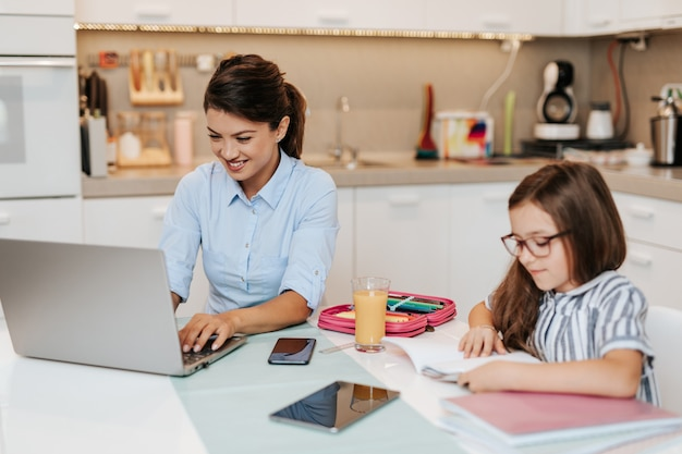 A mãe trabalha em casa devido ao coronavírus, enquanto a filha faz o dever de casa.