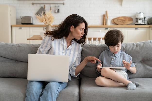 A mãe trabalhadora freelance ajuda o filho com o tablet a apontar o dedo para a tela digital enquanto trabalho remoto de casa