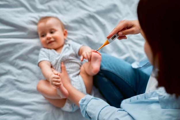 A mãe verifica a temperatura do filho doente, o recém-nascido está com febre. conceito de saúde do dia das mães. febre do bebê.