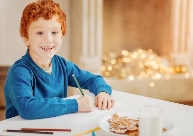 A magia é real. criança adorável ruiva sentado à mesa e escrevendo uma carta para seu papai noel favorito.
