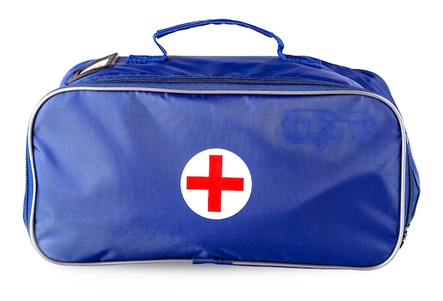 A maleta azul com uma cruz vermelha isolada no branco