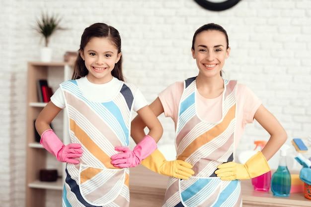 A mamã e a filha de sorriso limpam em casa.
