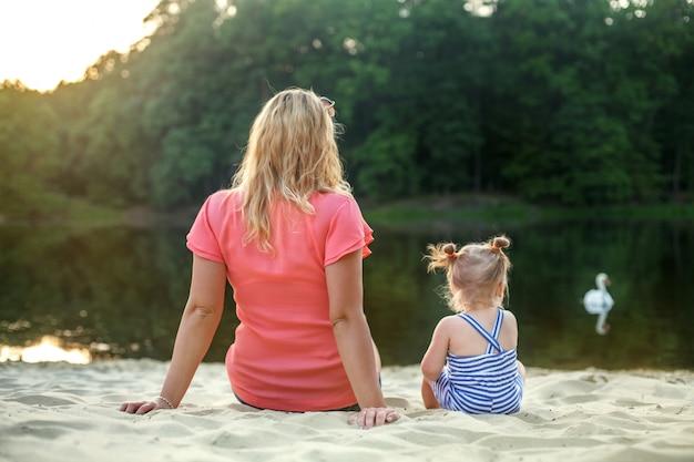 A mamã e a filha do bebê sentam-se e olham-se o lago. o conceito de infância, lazer e estilo de vida.