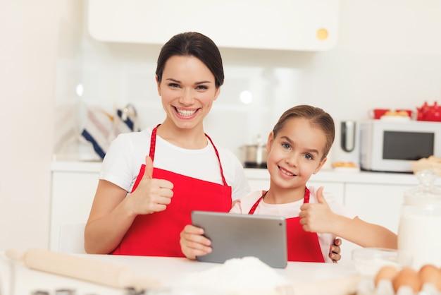 A mamã e a filha pequena cozinham junto na cozinha em casa.
