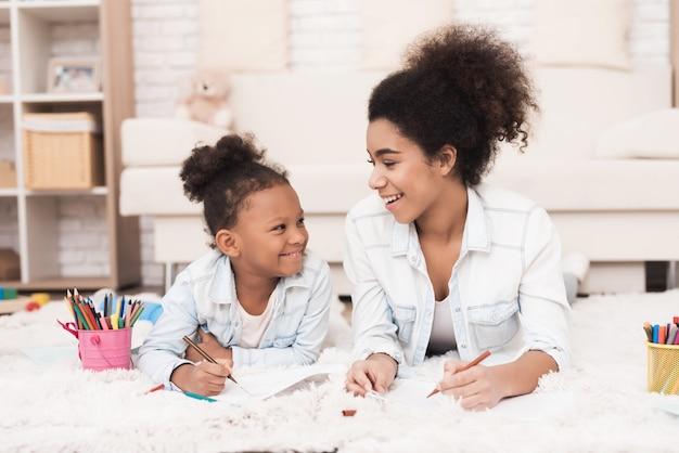 A mamã e a menina pequena do mulato encontram-se no assoalho com canetas de feltro.