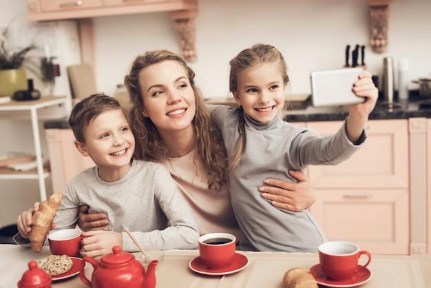 A mamã e as crianças felizes têm o chá na foto da tomada da cozinha.