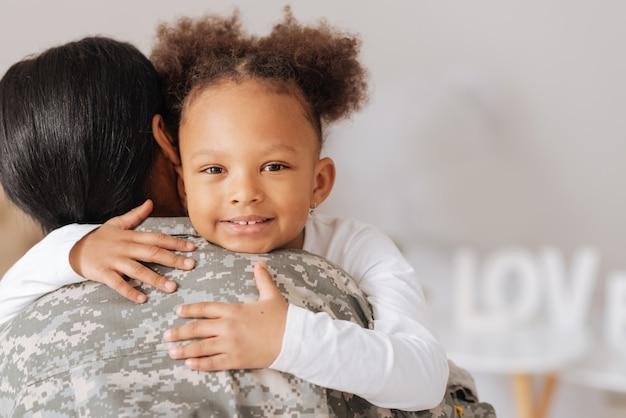 A mamãe está de volta. linda criança encaracolada positiva abraçando a mãe expressando sua felicidade depois de sentir muitas saudades dela