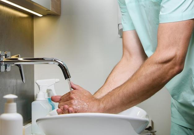 A maneira certa de lavar as mãos debaixo d'água para a equipe médica antes de trabalhar com pacientes infectados com coronovírus covid 19