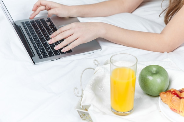 A manhã e o café da manhã de uma bela jovem na cama em casa com as mãos do laptop
