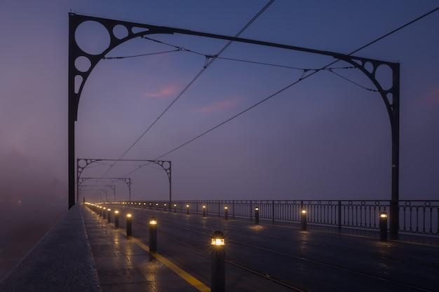 A manhã nublada antes do amanhecer em uma rua da cidade com trilhos de bonde e fileiras de lanternas baixas ao longo da estrada