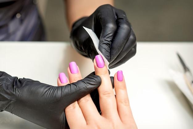 A manicure está limpando esmalte rosa nas unhas femininas após a manicure no salão de beleza