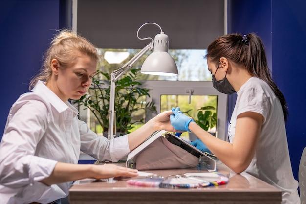 A manicure está se concentrando nas mãos de uma jovem que veio para o procedimento. na mesa de manicure estão as amostras de verniz com flores que estão disponíveis