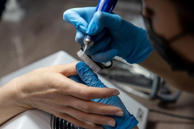 A manicure remove a poeira dos dedos da cliente com uma escova especial após o processamento das unhas