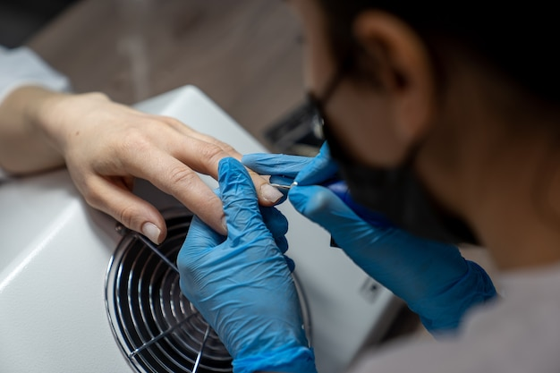A manicure trata as cutículas dos dedos da cliente com um bico especial na máquina