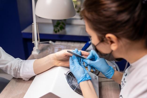 A manicure trata as unhas da cliente com uma lima especial