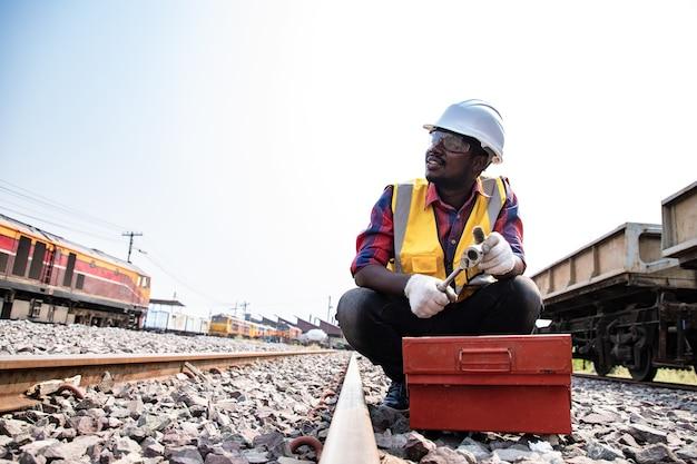 A manutenção de engenharia industrial africana bonita da américa latina prepara e mantém o equipamento para consertar o trem nas fábricas de garagem com uma chave