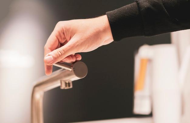 A mão abre a torneira de torneira de cozinha close-up