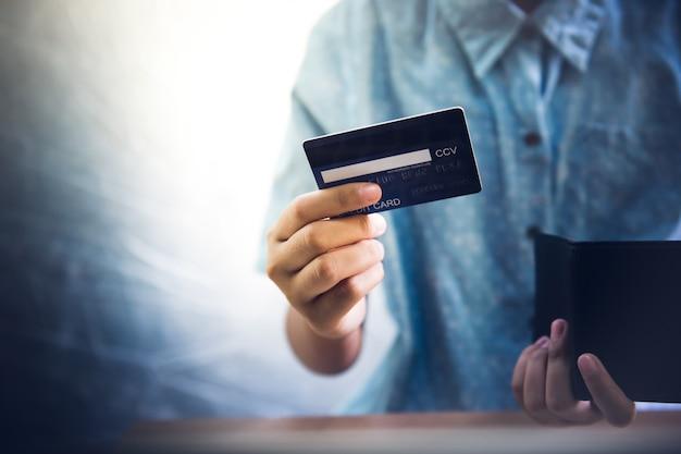 A mão adolescente usa um cartão de crédito. ela puxa a carteira. - imagens
