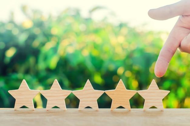 A mão aponta para a quinta estrela de madeira.