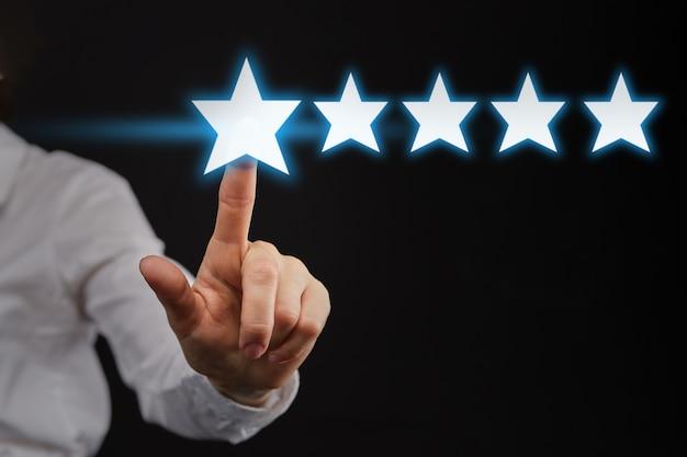 A mão aponta para cinco 5 estrelas como um conceito de melhor classificação ou classificação.