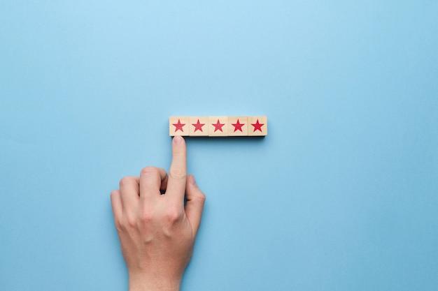A mão aponta para o conceito cinco estrelas de pontuação alta.