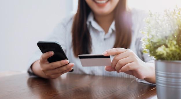 A mão asiática da mulher que guarda o cartão e o smartphone de crédito incorporam o código do pagamento para o produto.