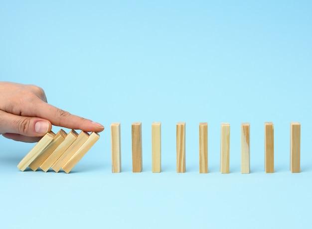 A mão com o dedo impede a queda de barras de madeira em uma superfície azul