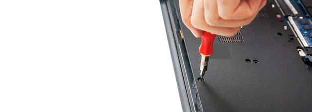 A mão com uma chave de fenda desmonte a caixa do laptop em partes para substituir e reparar.
